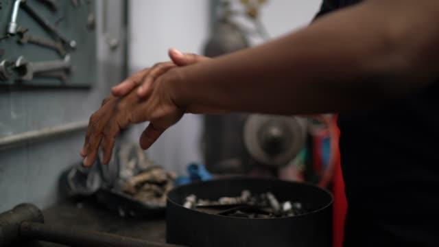 mechaniker mit alkohol-gel zu reinigen und waschen hand bei auto-reparatur - hygiene stock-videos und b-roll-filmmaterial