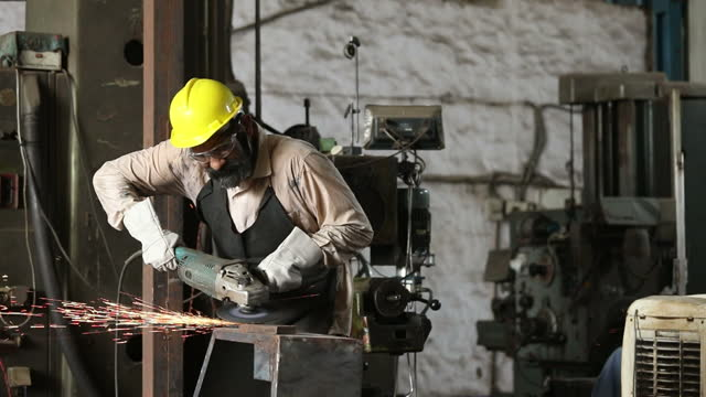 mechanic using circular saw grinder tool at factory - beard stock videos & royalty-free footage