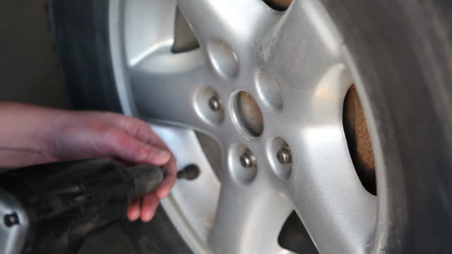 Mechanic Using Impact Wrench to Remove Wheel Lug Nuts