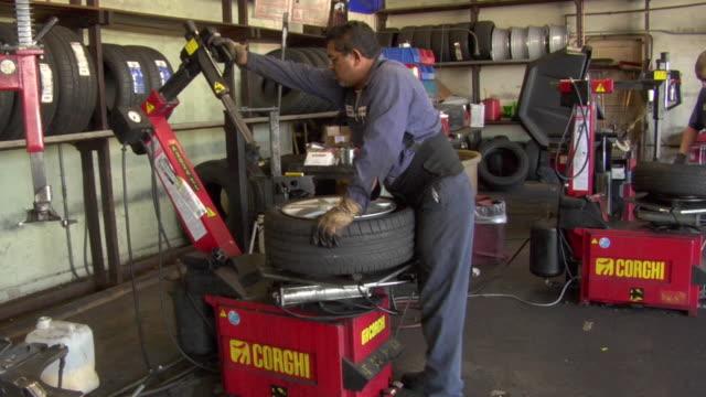 ms mechanic using machine to remove old tire / los angeles, california, usa - 中年の男性だけ点の映像素材/bロール