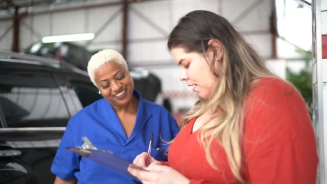 mechanic woman talking to her customer at auto car repair - customer focused stock videos & royalty-free footage