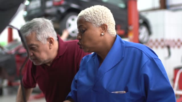 mechanic woman talking to her customer in car auto repair - inspector stock videos & royalty-free footage