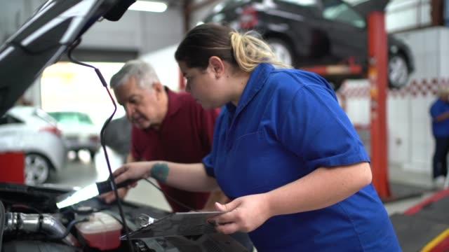 mechaniker frau im gespräch mit ihrem kunden in auto-auto-reparatur - automobilindustrie stock-videos und b-roll-filmmaterial