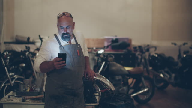 mechanic working in his motorcycle repair shop - completely bald stock videos & royalty-free footage