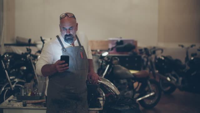 vídeos y material grabado en eventos de stock de mechanic working in his motorcycle repair shop - mecánico de coches