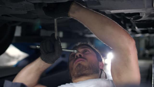 vidéos et rushes de mécanicien travaillant sur un véhicule dans un service de voiture. - mécanicien