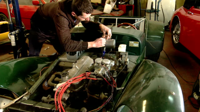 mechanic working on British Lotus 7 sports car