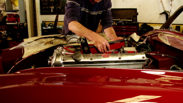 mechanic working on jaguar xk140 classic car engine - restoring stock videos and b-roll footage