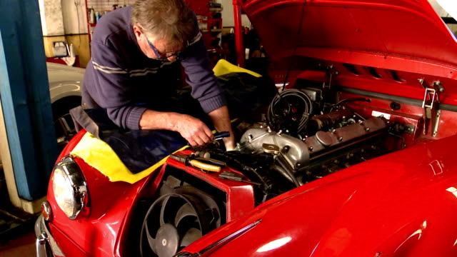Mechanic working on Jaguar XK150 classic car engine