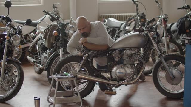 mechanic working on motorcycles - repair shop stock videos & royalty-free footage