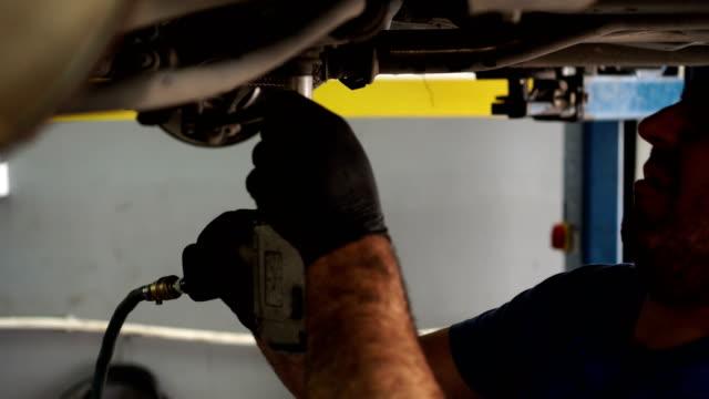 車の下でメカニックの作業をクローズ アップ - 作業道具点の映像素材/bロール