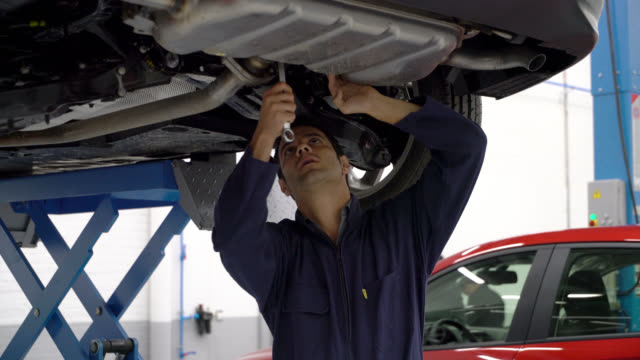 mechaniker arbeiten unter einem auto mit einem werkzeug und etwas anpassen - in bodenhöhe stock-videos und b-roll-filmmaterial