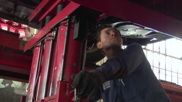 ms mechanic works underneath car / los angeles, california, usa - 中年の男性だけ点の映像素材/bロール