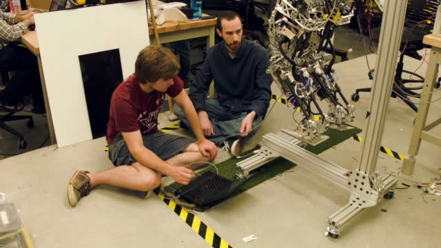 mechanical and electrical engineering students from team valor build and test the escher they are building for the defense advanced research projects... - ministero americano della difesa video stock e b–roll