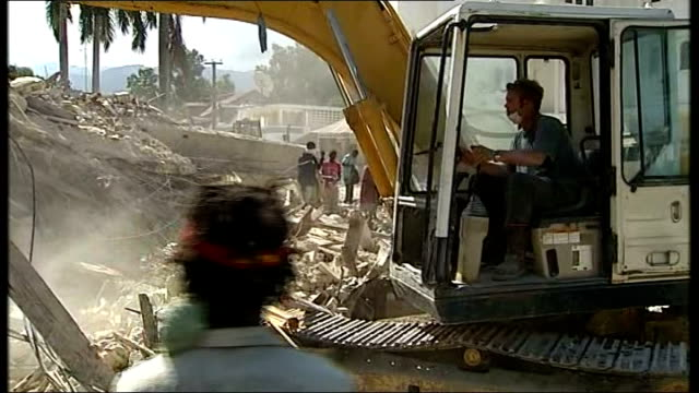 Mechanical digger and survivors with hammers breaking up the remains of a collapsed hotel Survivor towards holding shoes found in the rubble sawing...