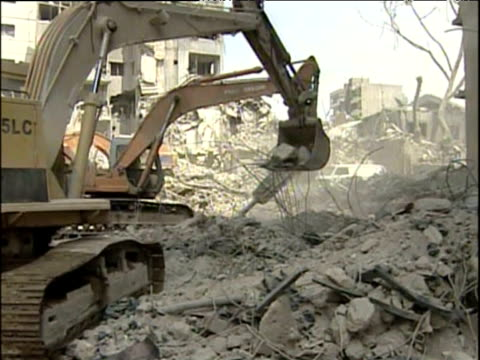stockvideo's en b-roll-footage met mechanical digger removes rubble from bombed streets lebanon 30 sep 06 - bouwvoertuig
