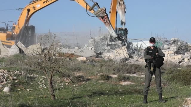 mechanical excavators guarded by israeli security forces demolish a palestinian house built within area c on the southern outskirts of the city of... - human settlement stock videos & royalty-free footage