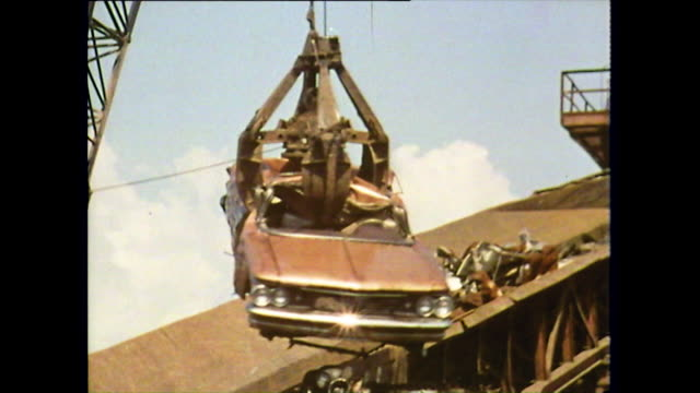 mechanical grabber picks up rusty car in scrapyard; 1972 - vrak bildbanksvideor och videomaterial från bakom kulisserna