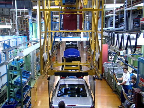mechanical hoist carries car and drops into place on production line assembly engineers work on vehicle's development attaching fender as hoist withdraws bremen - ingenieurwesen stock-videos und b-roll-filmmaterial