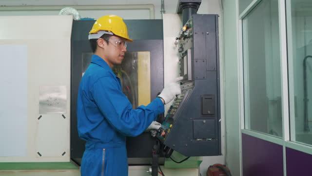 stockvideo's en b-roll-footage met werktuigbouwkundige medewerker die gegevens invoert in cnc-freessmachine in de fabriek in de gereedschapswerkplaats in de metaalbewerkingsindustrie. - drukknop
