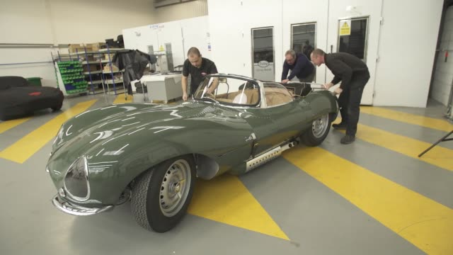 mechanics and workers working on and moving the jaguar xkss supercar continuation model at the jaguar classic workshop in coventry, u.k., on... - コベントリー点の映像素材/bロール