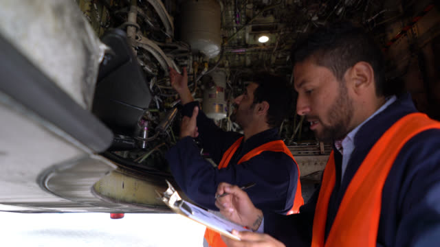 mechanics checking airplane and going over a checklist talking and looking very focused - air vehicle stock videos & royalty-free footage