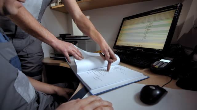 stockvideo's en b-roll-footage met mechanics doing paperwork - driekwartlengte