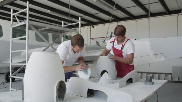 mechanics in aviation paint shop sanding propeller spinners prior to painting them, RED R3D 4k