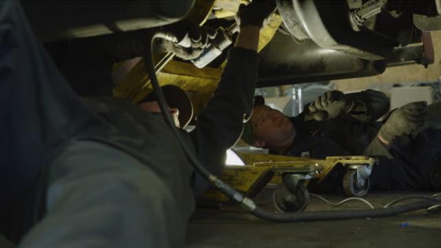 mechanics laying under truck using power tool / aurora, utah, united states - mechanic stock videos & royalty-free footage