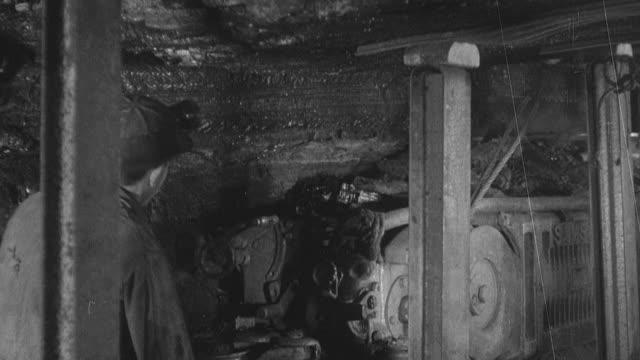 vidéos et rushes de 1954 montage mechanics performing maintenance tasks on coal mining equipment / united kingdom - 1954