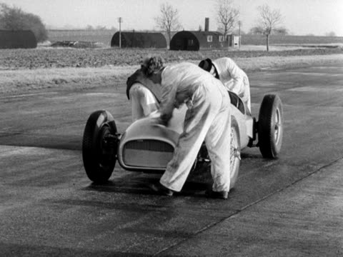 mechanics polish the new brm racing car prior to a test run on a disused airfield - 試運転点の映像素材/bロール