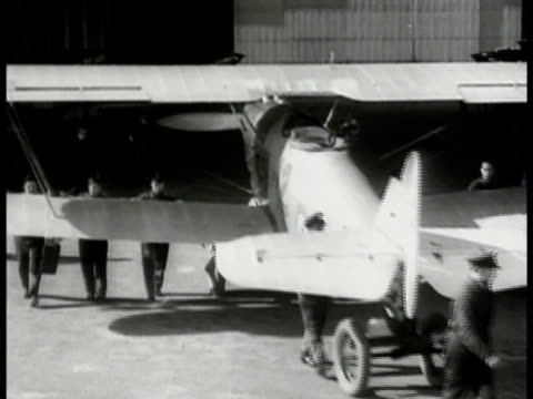 mechanics pulling biplane out of hangar. mechanics working on engine of airplane 'rolls-royce.' biplanes in formation passing overhead. overhead:... - 1940 stock videos & royalty-free footage