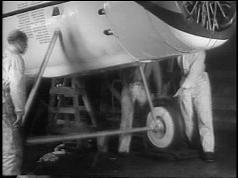 vidéos et rushes de b/w 1935 mechanics testing landing gear of winnie mae prop airplane in hangar / newsreel - 1935