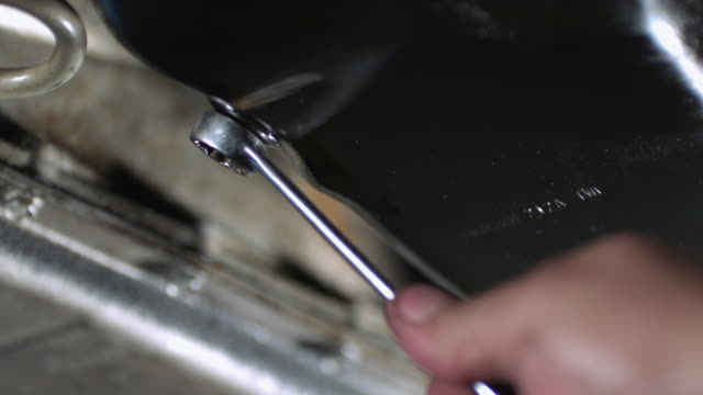 cu slo mo  mechanics tightening nut with wrench on oil pan  / bergenfield, , new jersey, usa   - wrench stock videos & royalty-free footage