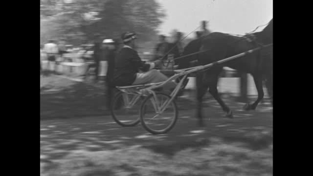 Med close up Elizabeth McCaw Dillard 'Blitz' Reynolds rides off on sulky cart to begin harness race as husband R J Reynolds Jr walks out of frame / R...