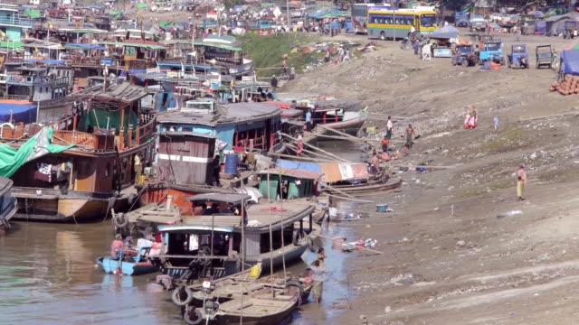 med shot. boats at irrawaddy river shore in madalay, myanmar - spoonfilm stock-videos und b-roll-filmmaterial