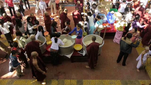 med shot. monk feeding in amarapura, myanamar - ボランティア点の映像素材/bロール