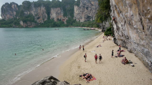 med shot. rockclimbers at beach in tonsai, thailand. - spoonfilm stock-videos und b-roll-filmmaterial