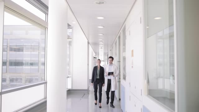 medic and consultant in a meeting walking through hospital - 廊下点の映像素材/bロール