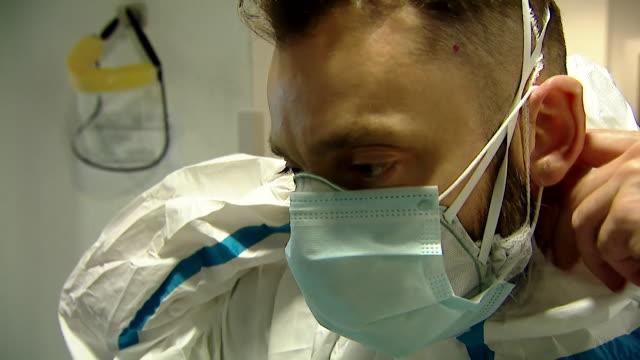 medic in puerta de hierro hospital, madrid, puts on full ppe before entering the icu ward treating coronavirus patients - getting dressed stock videos & royalty-free footage