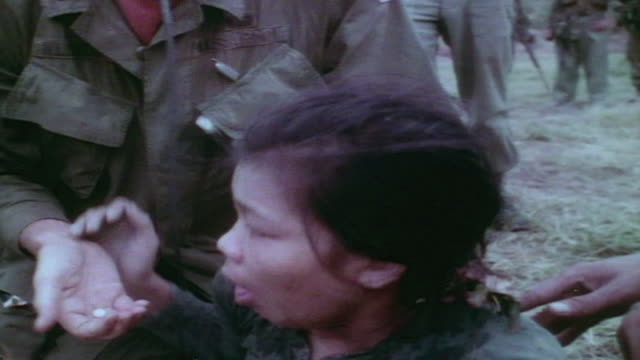 medic providing medicine and care to sick viet cong captive while intelligence officer supports her shoulders and talks / vietnam - desaturated stock videos & royalty-free footage