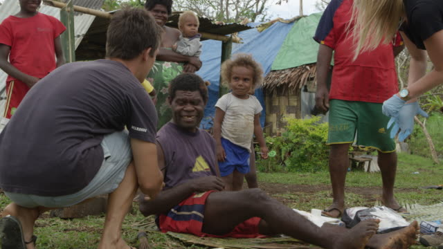 vanuatu - march 31, 2015: medic shakes hands with patient, patient gives thumbs up sign, family watches - rebuilding stock videos & royalty-free footage