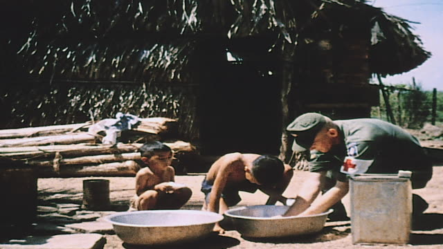 Medic washing village child's hair with bowl of soapy water / Vietnam