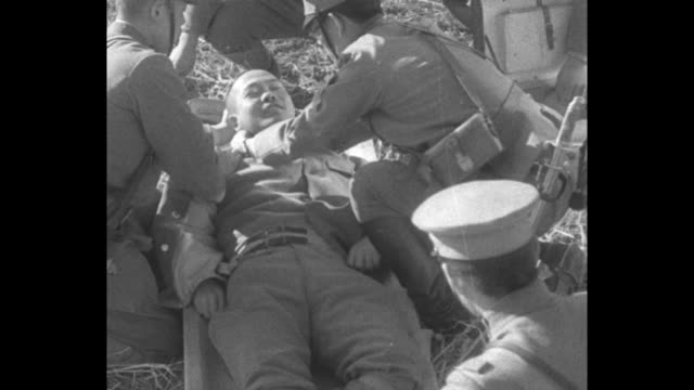 medic wraps bandage around wounded japanese soldier's neck as the patient lies on a stretcher on the ground after the japanese army's arrival in... - 満州地方点の映像素材/bロール