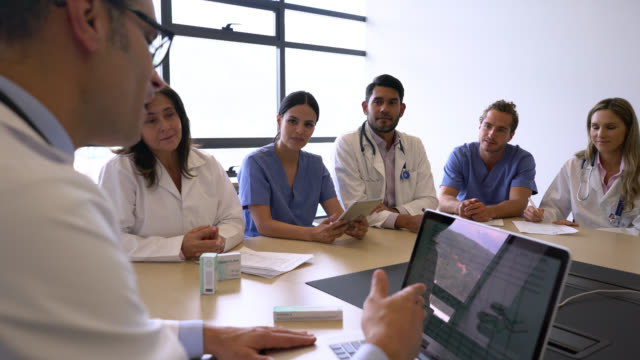 vidéos et rushes de conseil médical dans une réunion à l'hôpital tous prêter attention au médecin parlant tout en regardant l'écran de l'ordinateur portable - enthousiaste