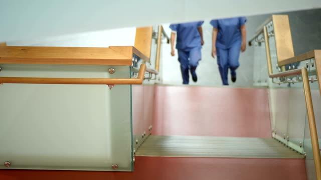 medizinische kollegen unterhalten sich im treppenhaus des hospital - treppe stock-videos und b-roll-filmmaterial