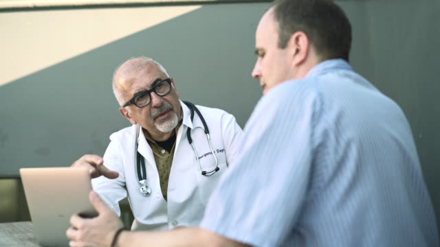 Medical consultation: the doctor, senior silver haired man, talking with the patient, adult Caucasian man.