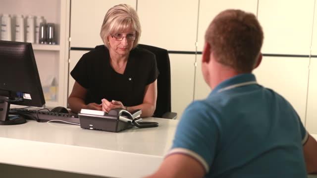 vídeos y material grabado en eventos de stock de consulta clínica - recepcionista
