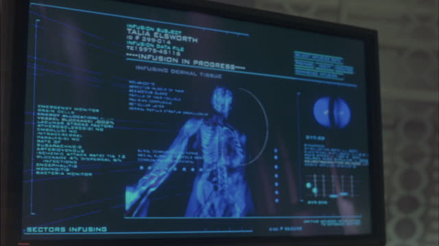 Medical data flashes and scrolls by on a flat screen.