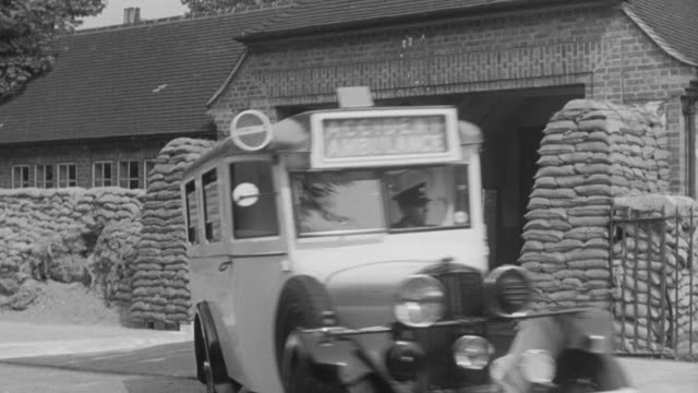 1940 montage medical dispatcher receiving and relaying messages in emergency communication center, ambulance departing and arriving at hospital, and emt personnel offloading patient from ambulance and into hospital / united kingdom - nhs stock-videos und b-roll-filmmaterial
